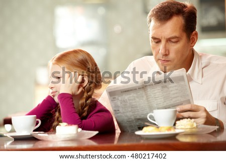 Little girl sitting back to her father who is reading paper