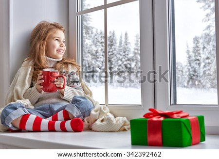 little girl sitting by the window and looking at the winter forest - stock photo