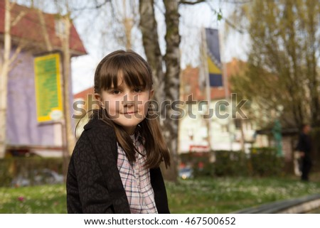 little girl sitting in a park