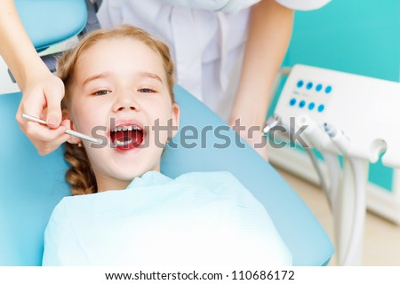 Little girl sitting in the dentists office - stock photo