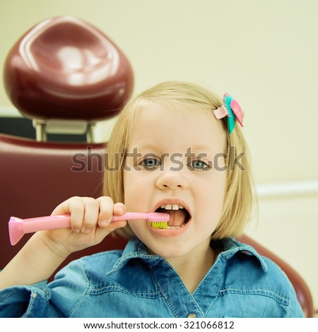 Little girl sitting in the dentists office brushes teeth - stock photo