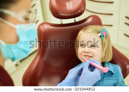 Little girl sitting in the dentists office. The dentist brushes teeth to the little girl - stock photo