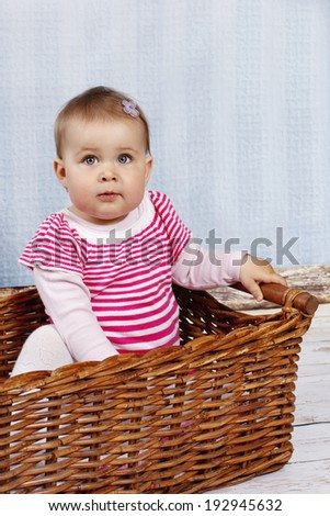 Little girl sitting inside the wicker basket