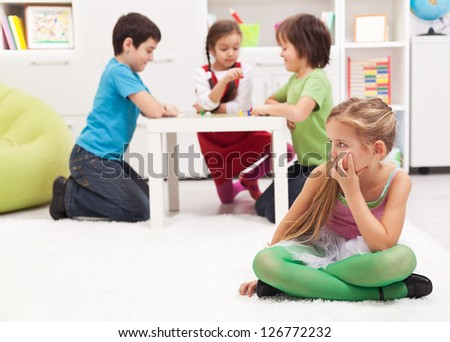 Little girl sitting lonely - feeling excluded by the others - stock photo