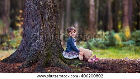 Little girl sitting near pine-tree with her teddy bear - stock photo