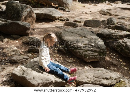 Little girl sitting on a big stone