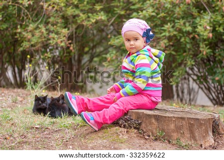 Little girl sitting on a stump. Two cats in the background. - stock photo