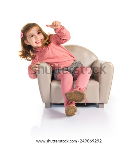 Little girl sitting on armchair with thumb up - stock photo