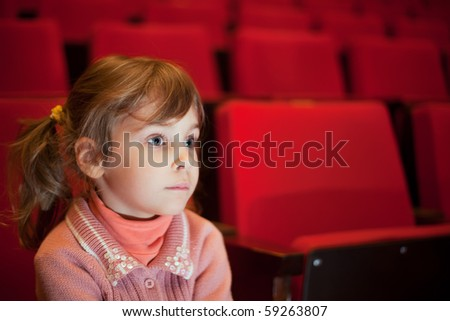 little girl sitting on armchairs at cinema, steadfastly looking - stock photo