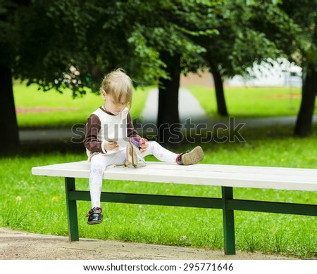 little girl sitting on bench and reading a book - stock photo
