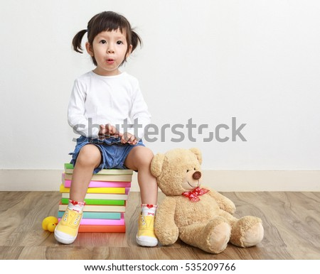 Little girl sitting on books and toy teddy bear