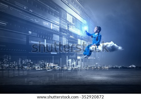 Little girl sitting on cloud and touching virtual panel with finger - stock photo