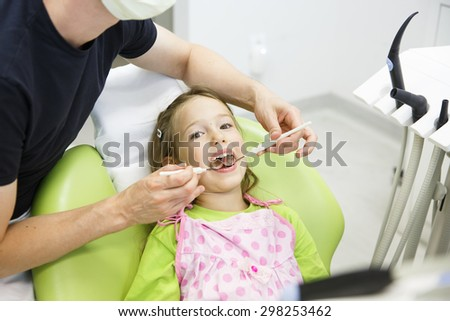 Little girl sitting on dental chair in pediatric dentists office, being examined by her dentist. Early prevention, oral hygiene and milk teeth care concept.  - stock photo