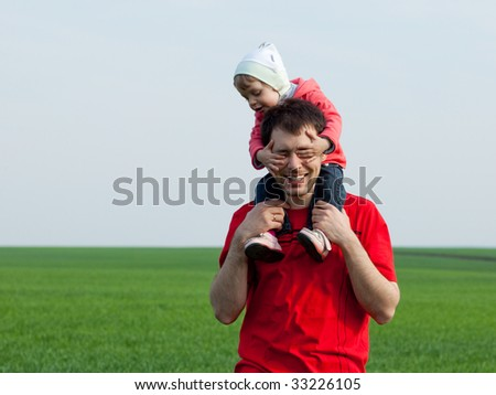 Little girl sitting on father's shoulders closes his eyes with her hands - stock photo