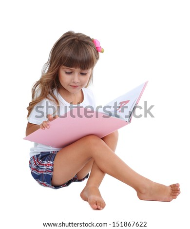 Little girl sitting on floor with book isolated on white