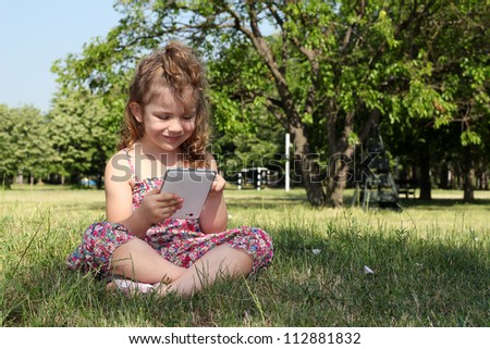 little girl sitting on grass and play with tablet pc - stock photo