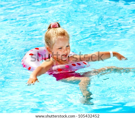 Little girl sitting on inflatable ring in swimming pool.