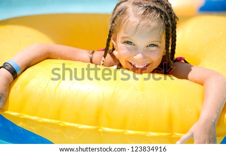 Little girl  sitting on inflatable yellow ring in swimming pool.