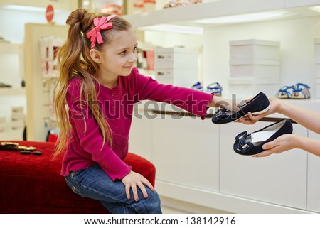 Little girl sitting on ottoman, takes pair of shoes from hands of seller - stock photo