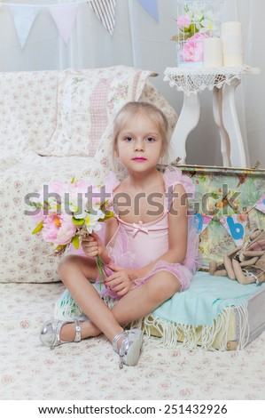 Little girl sitting on small bag with flowers in pink dress - stock photo