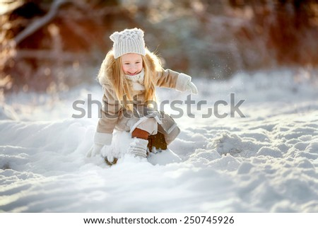 little girl sitting on snow and playing in winter - stock photo