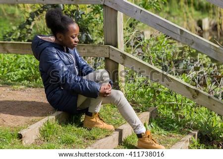 Little girl sitting on steps near railing gazing forward - stock photo
