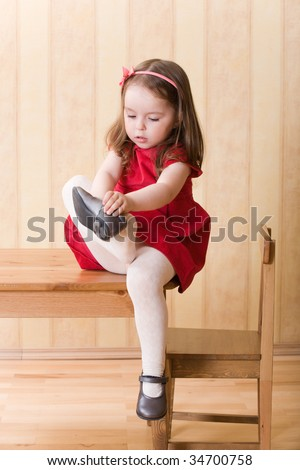 Little girl sitting on table and put on one's shoes - stock photo