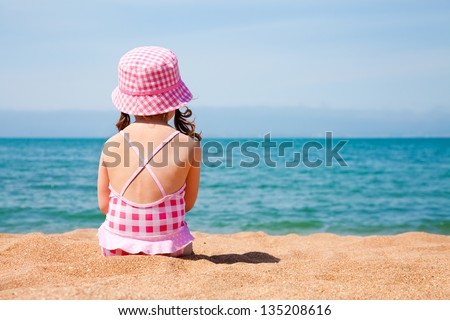 little girl sitting on the beach and sunbathe in the sun - stock photo