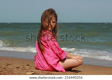 Little girl sitting on the beach with his back to the camera in summer sunny day Kerch, Crimea, Russia