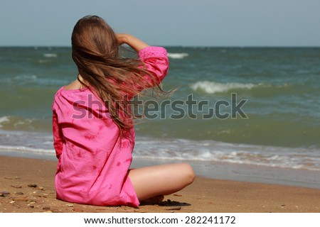 Little girl sitting on the beach with his back to the camera in summer sunny day Kerch, Crimea, Russia - stock photo