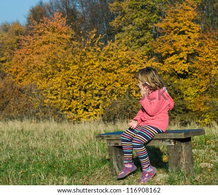Little girl sitting on the bench in the woods,speaks by phone - stock photo