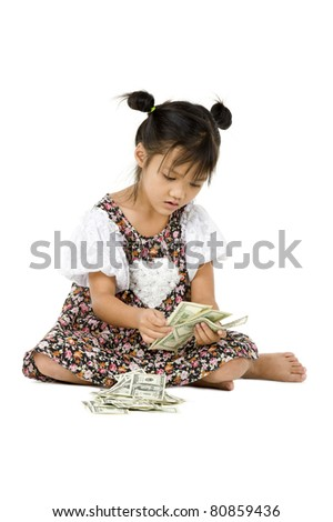 little girl sitting on the floor counting money, isolated on white background - stock photo