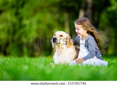 Little girl sitting on the grass with dog in the summer park