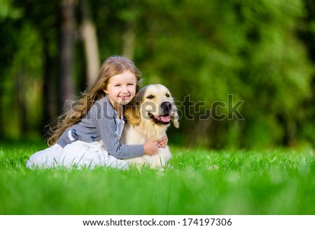 Little girl sitting on the grass with golden retriever in the summer park - stock photo