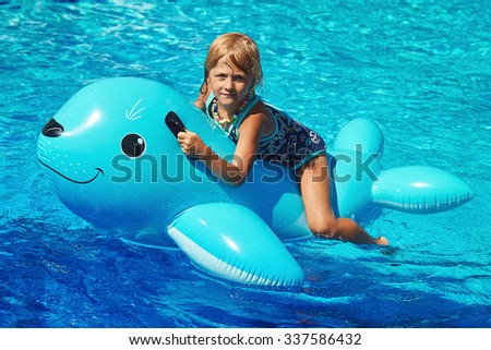 Little girl sitting on the inflatable Sea Lion in the swimming pool - stock photo