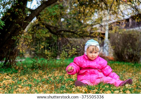 little girl sitting on the lawn in autumn - stock photo