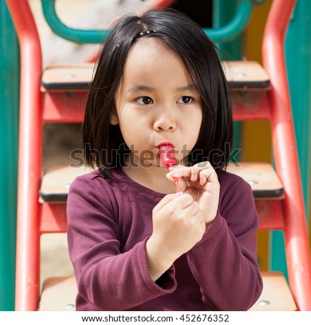 Little girl sitting on the slide and eating a lollipop