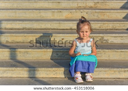Little girl sitting on the stairs