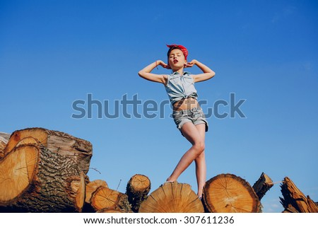 little girl sitting on the wood style pin up in jeans clothes - stock photo