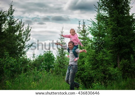 Little girl sitting on your dad shoulders outdoor in the woods during the summer