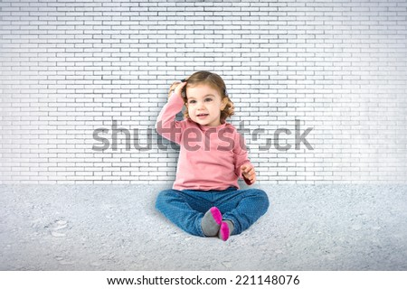 Little girl sitting over textured background