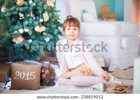 little girl sitting under the Christmas tree