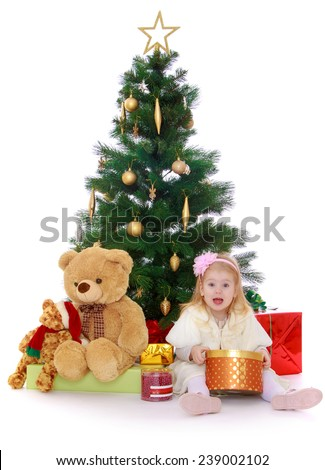 little girl sitting under the tree and holding a round box with a gift.Studio photo, isolated on white background. - stock photo