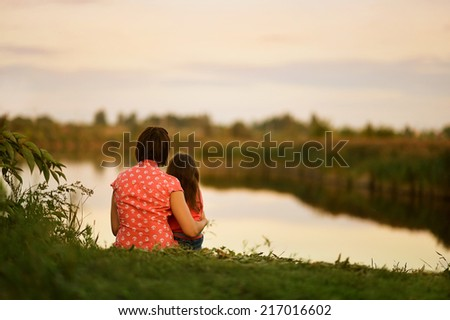 Little girl sitting with her mother near the lake,back view - stock photo