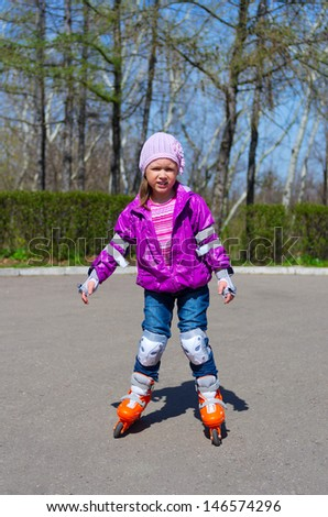 Little girl skating on roller skates at park