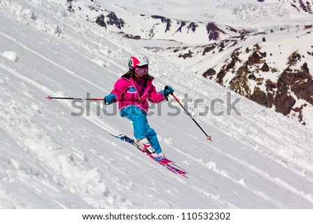 Little girl skier rides in the soft snow on a steep hill, on a sunny day - stock photo