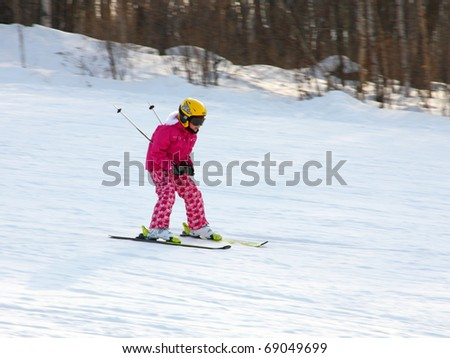 Little girl skiing downhill in winter equipment - stock photo
