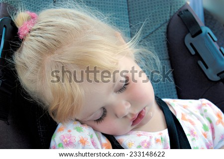 little girl sleeping and drooling in a car seat with seat belt  - stock photo