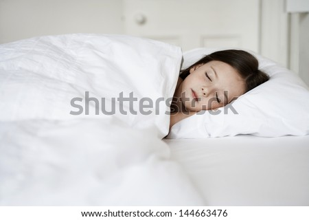 Little girl sleeping in bed cover with white blanket - stock photo