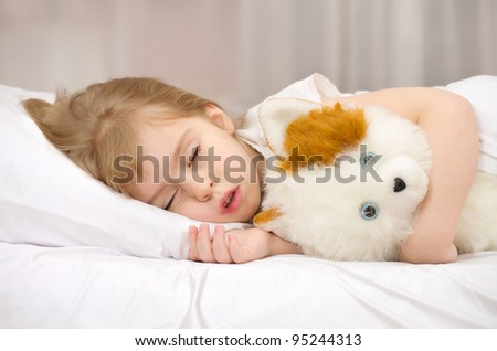 Little girl sleeping in bed with a soft toy. - stock photo